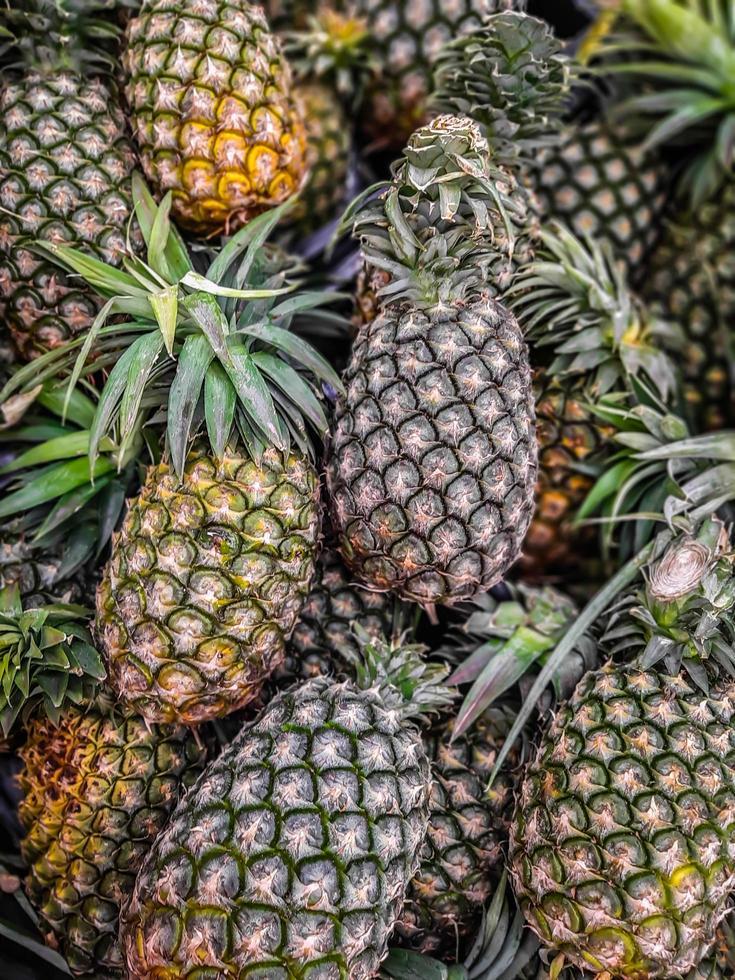 una gran cantidad de fondo de frutas de piña, frutas tropicales a la venta foto
