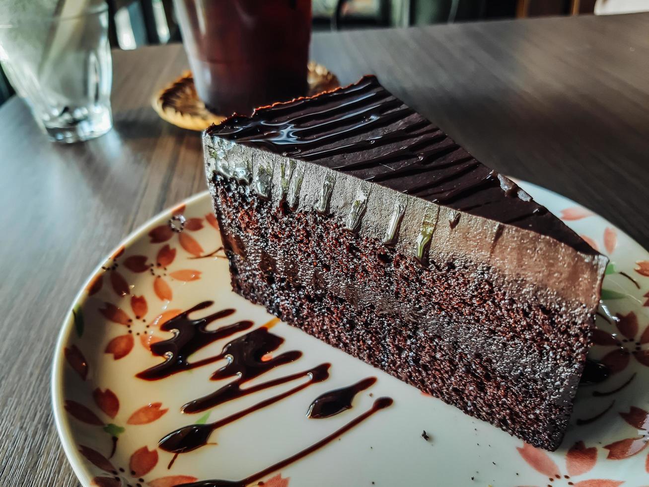 plato con rebanada de sabroso pastel de chocolate casero en la mesa, delicioso pastel de chocolate. pedazo de pastel en un plato. comida dulce. postre dulce. de cerca. foto