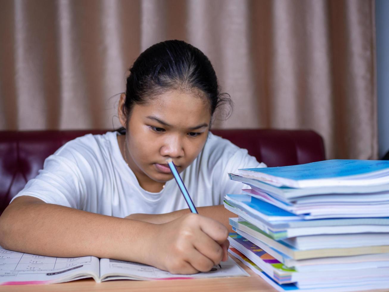 chica haciendo los deberes en una mesa de madera. foto