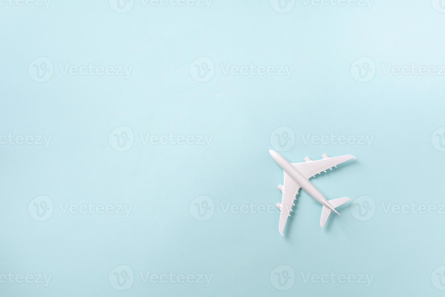 avión blanco, avión sobre fondo de color azul pastel con espacio de copia. vista superior, endecha plana. diseño de estilo minimalista. viajes, concepto de vacaciones foto