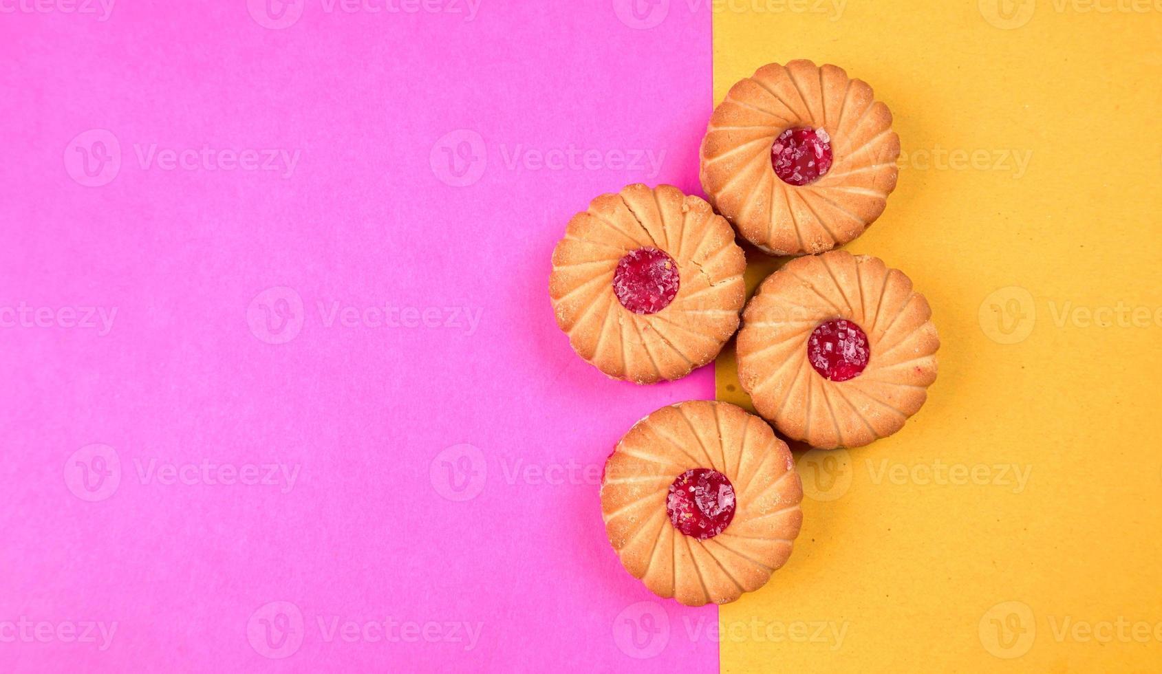 Vista superior de galletas de mermelada sobre fondo rosa y amarillo. galletas de sándwich o galletas de crema aisladas. foto