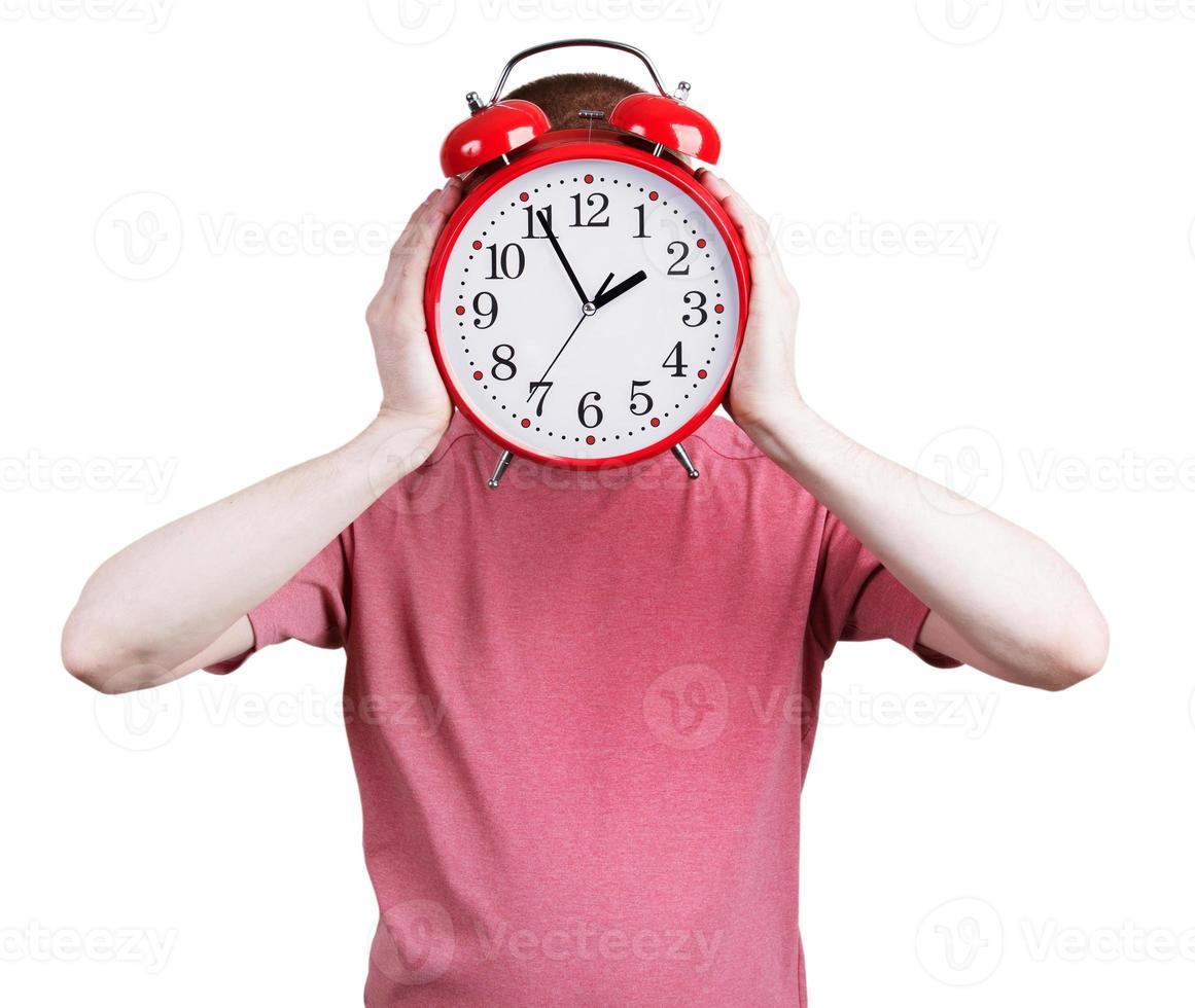 hombre con una camisa rosa con un reloj despertador foto