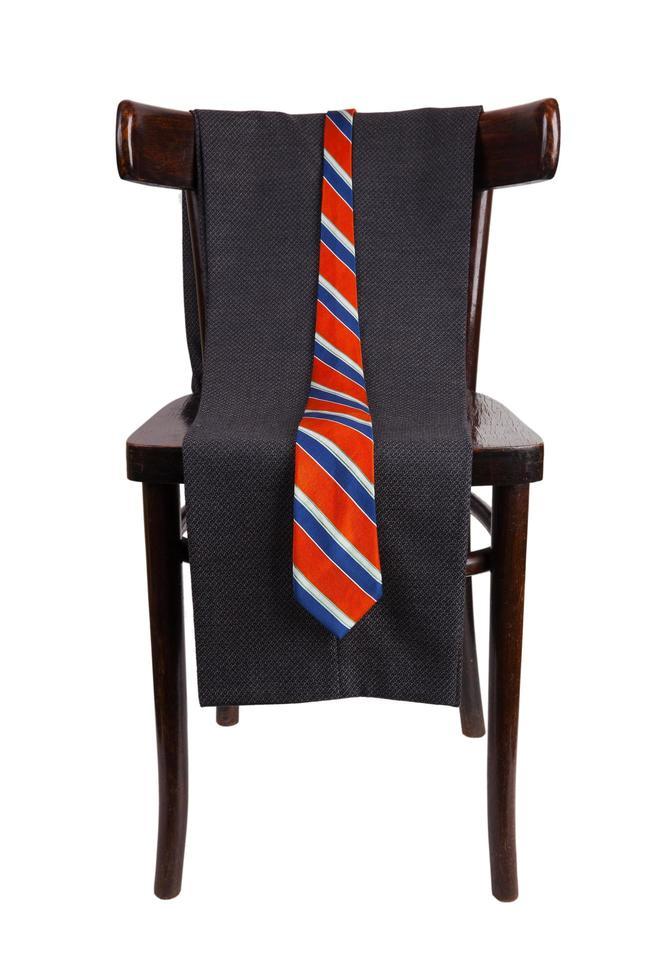 pantalones y corbata colgando de una silla foto