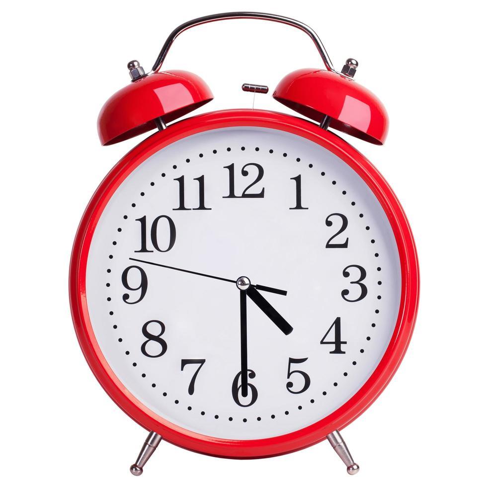 reloj despertador redondo muestra las cuatro y media foto