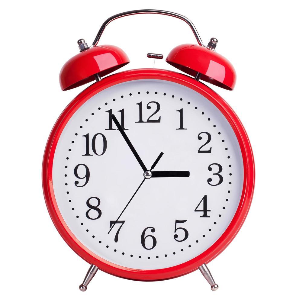 El despertador redondo muestra cinco minutos para las tres. foto