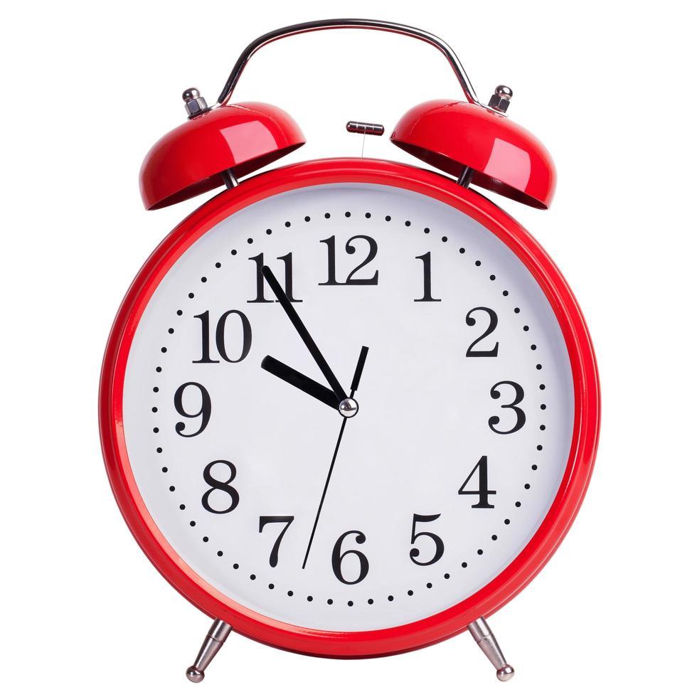 El despertador rojo redondo muestra cinco minutos para las diez. foto