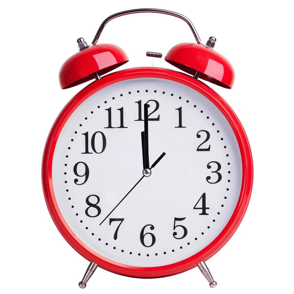 El despertador rojo muestra cinco minutos para las dos. foto