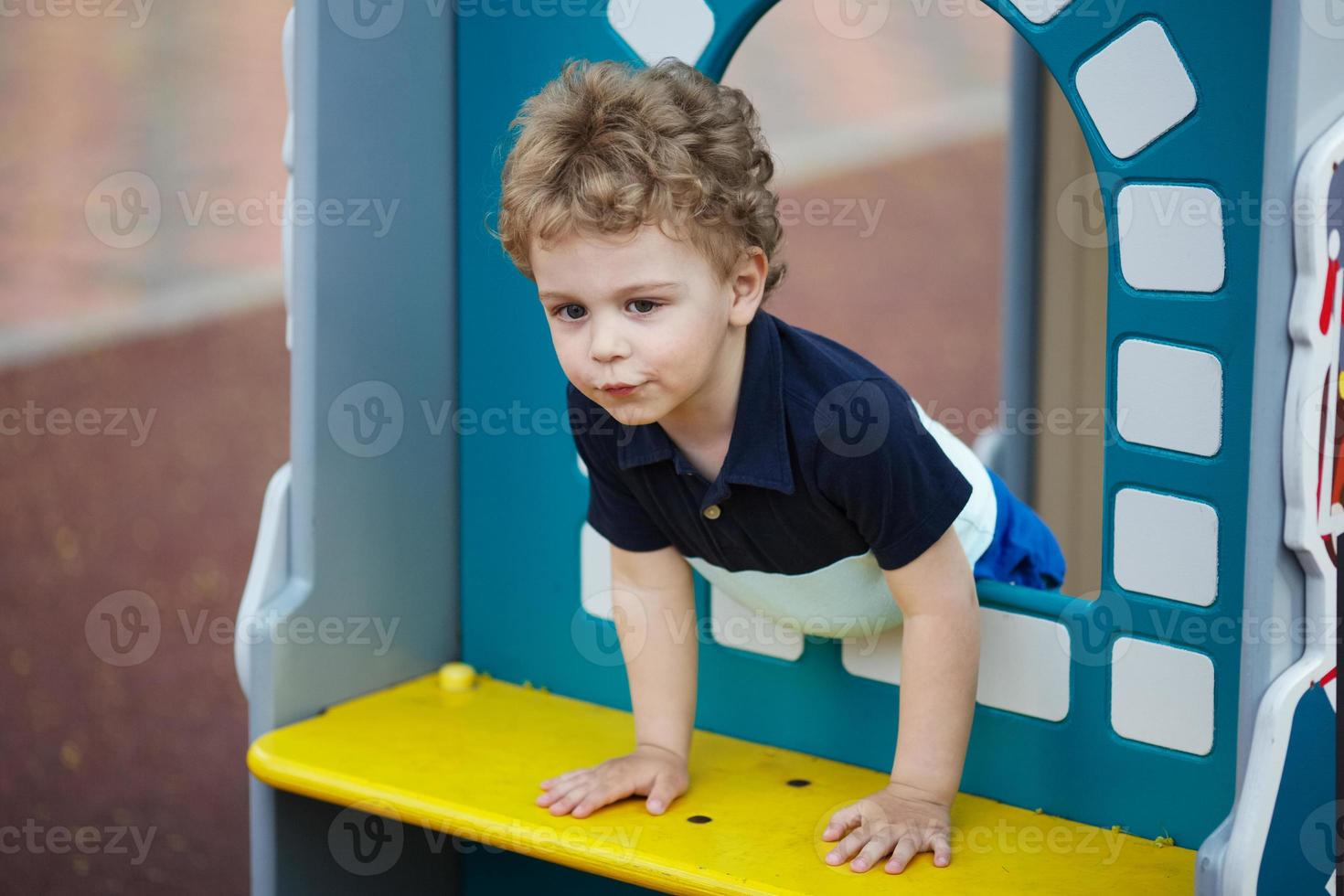 niño pequeño está jugando en el patio de recreo foto