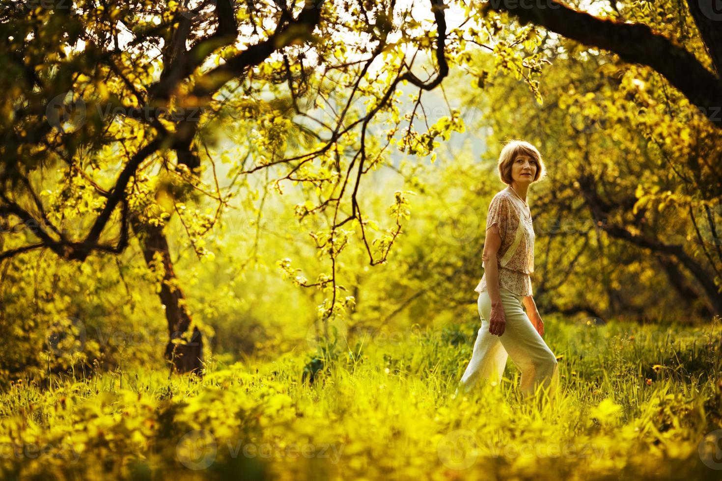 mujer caminando en el huerto de manzanas de verano foto