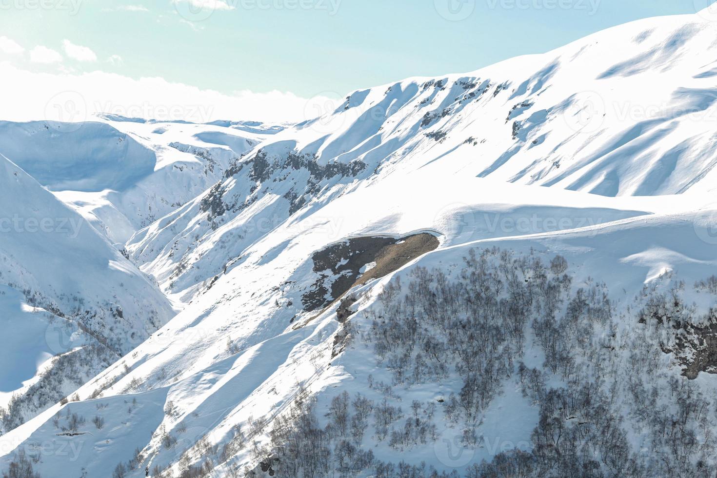 montañas con caminos de esquí de nieve y árboles. foto