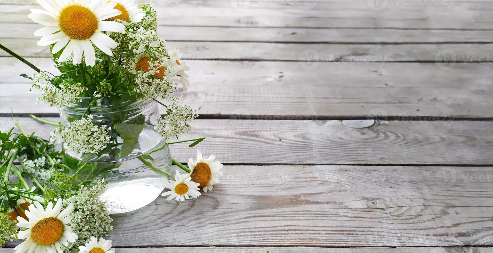 ramo de margaritas. Soporte de manzanilla de flores silvestres en un jarrón. fondo de madera, vista superior. foto