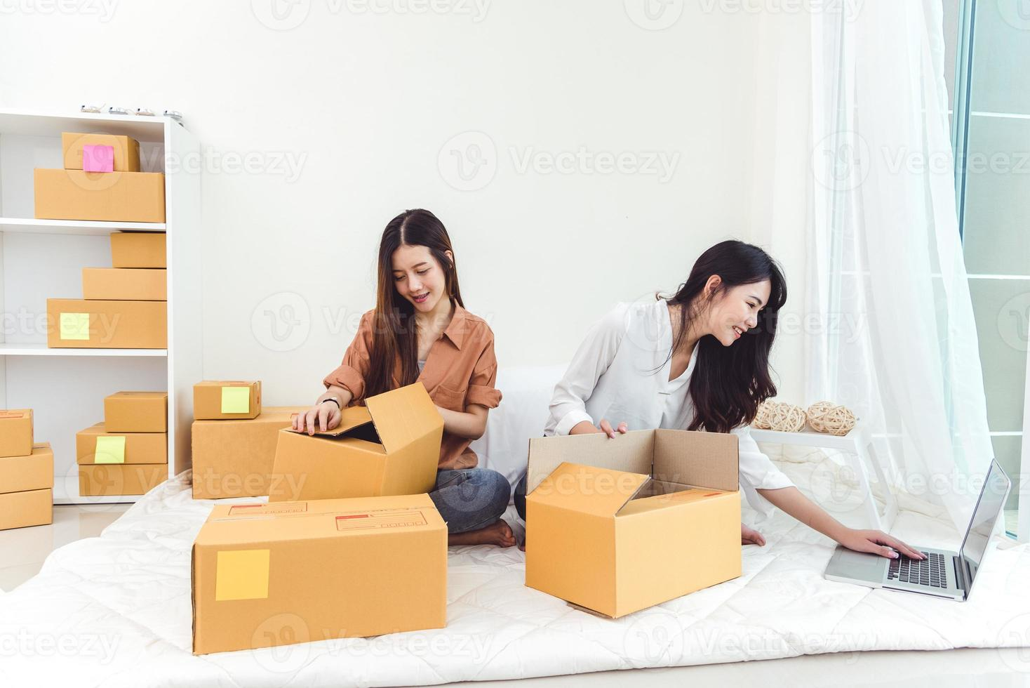 Young Asian woman startup small business entrepreneur SME distribution warehouse with parcel mail box. Owner home office concept. Online marketing and product packaging and delivery service photo