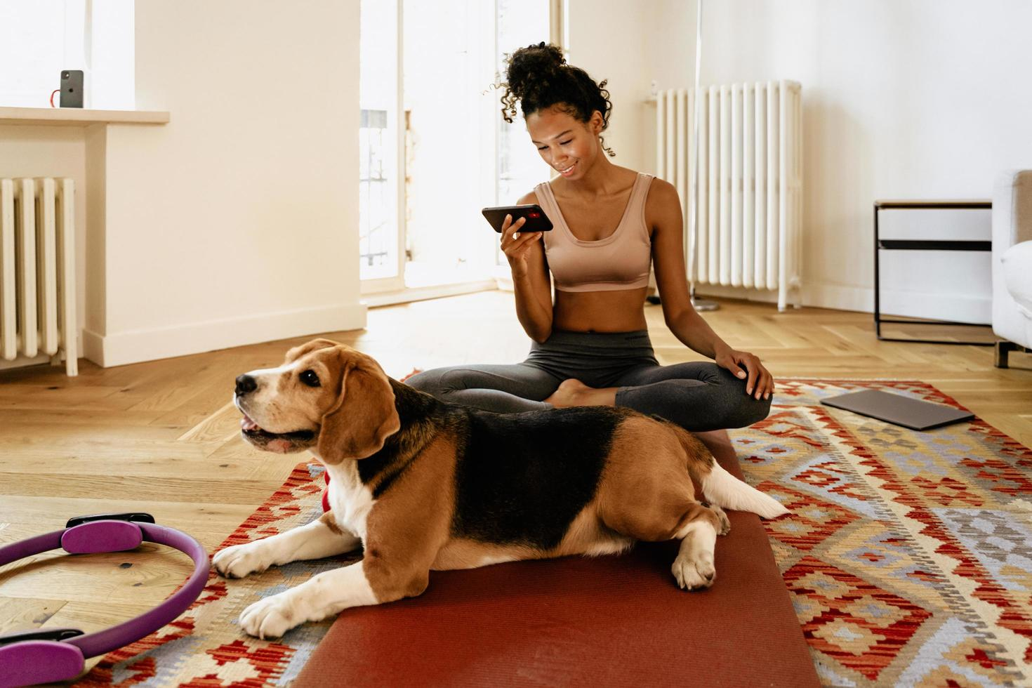 Black young woman using cellphone while sitting with her dog on mat photo