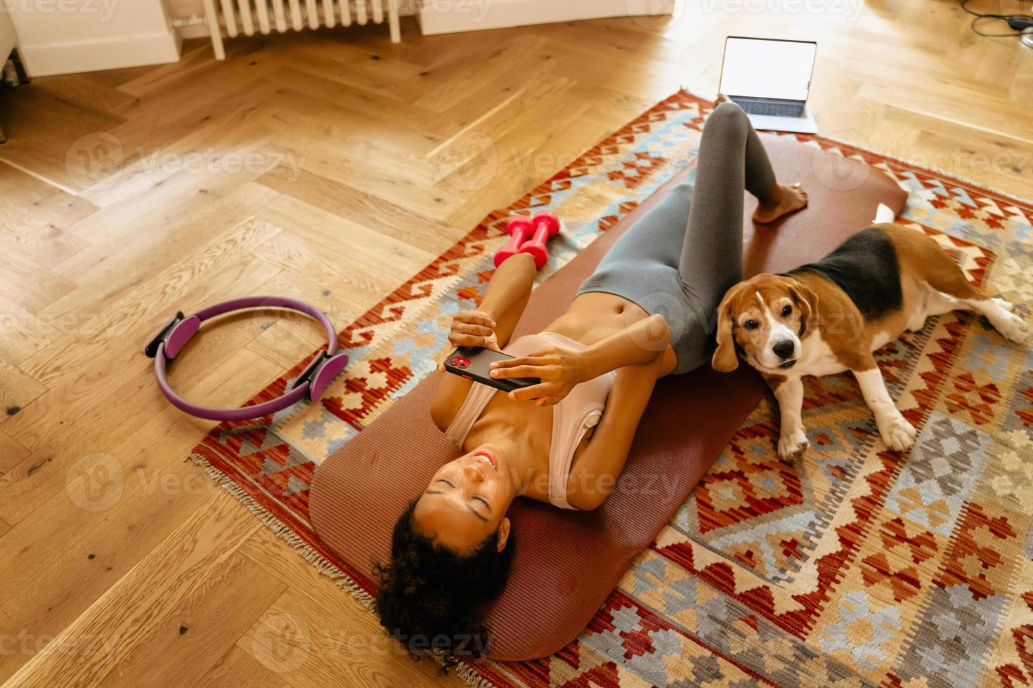 Black young woman using cellphone while resting after yoga practice photo