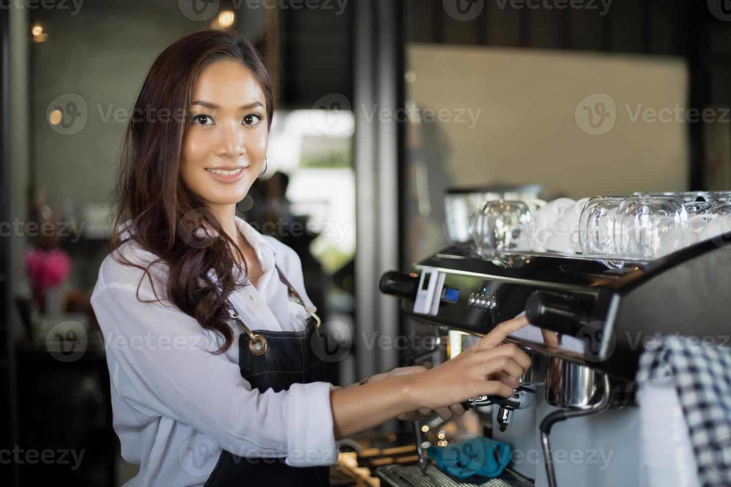 Asian women Barista smiling and using coffee machine in coffee shop counter - Working woman small business owner food and drink cafe concept photo