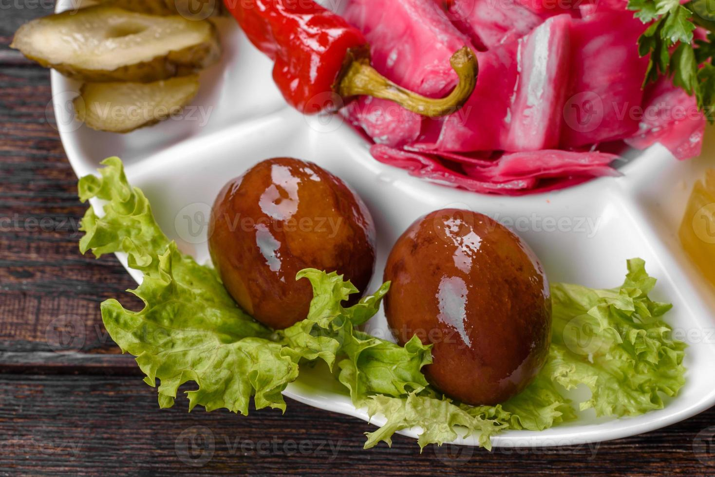 Deliciosos pepinillos picantes cortados en un plato para servir foto
