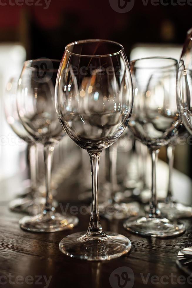copas de vino vacías. Hermosas copas nuevas para vino de soporte de vidrio en filas pares sobre una mesa de madera en un restaurante. enfoque selectivo foto