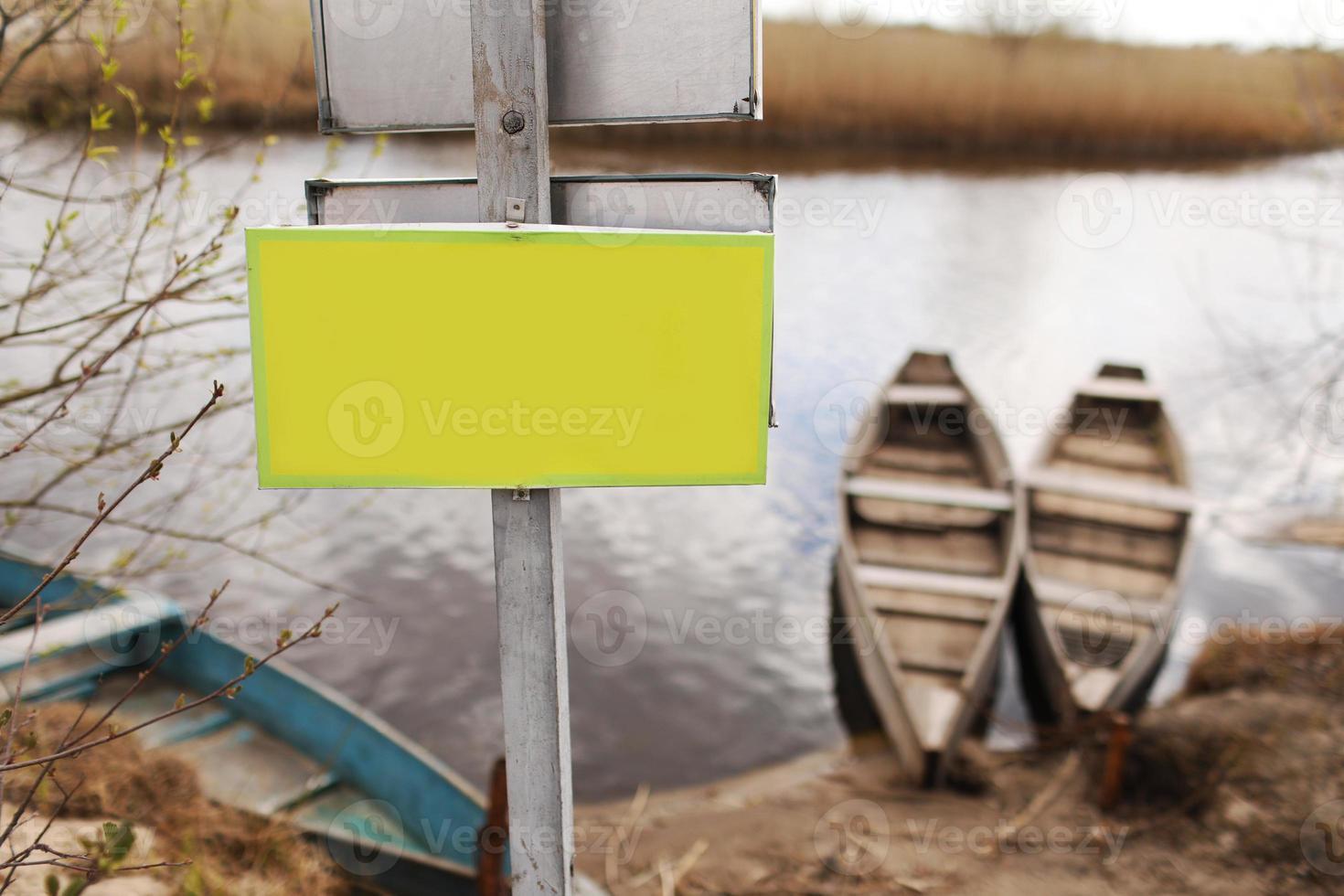Placa amarilla para inscripción sobre el césped junto al río y el fondo de los barcos a principios de la primavera foto