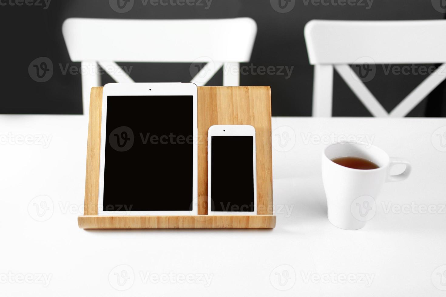 una tableta blanca y un teléfono inteligente en un soporte en un lugar de trabajo de oficina de mesa blanca. taza de té en el lugar de trabajo foto