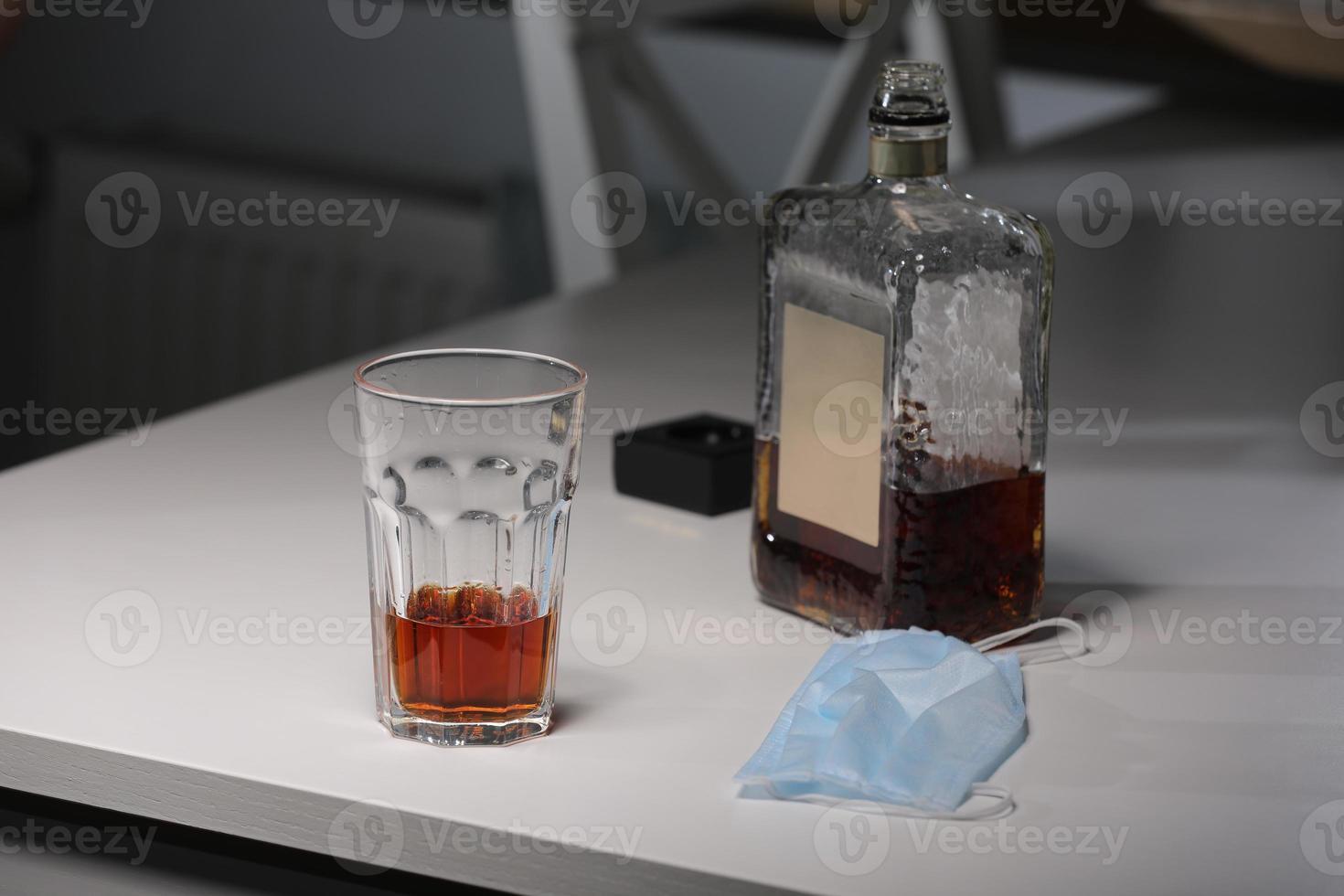 vaso con alcohol, botella de whisky y mascarilla médica sobre la mesa. concepto de eventos sociales cancelados durante la cuarentena por el virus de la corona y la pandemia foto
