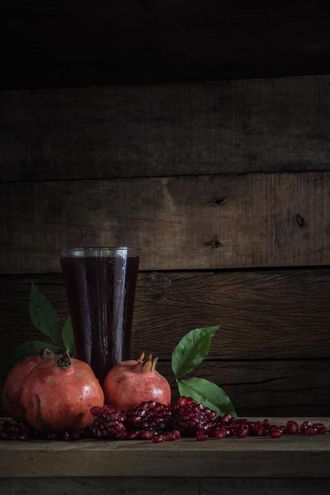 imagen de naturaleza muerta y seleccione foco de granada con jugo en vaso y pila de semillas en la plancha con poca luz. foto