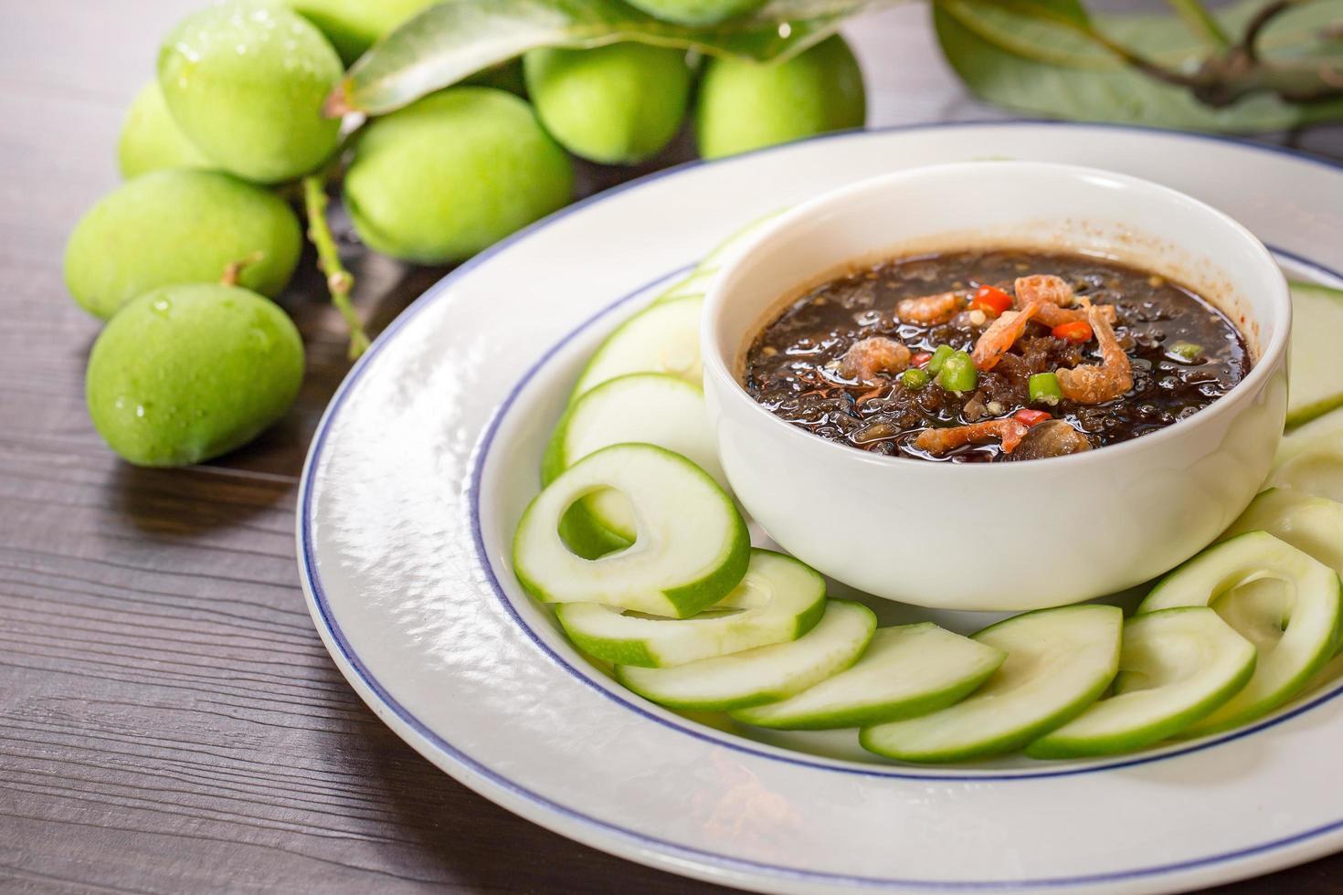 Mangos crudos salsa agria y dulce mezclar pasta de camarones, snack tailandés en plato blanco el enfoque selectivo foto
