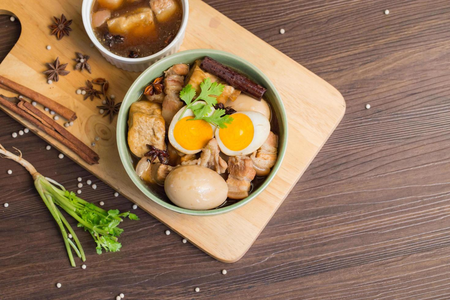 huevos y cerdo dulce con tofu frito, hervido en salsa marrón y en un tazón blanco sobre una vieja plancha de madera marrón. foto