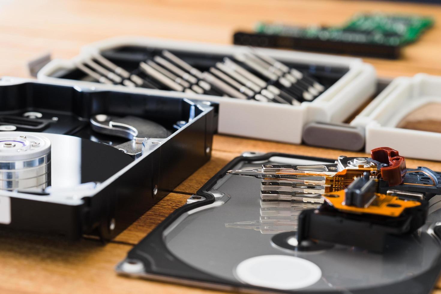 Unidad de disco duro desmontada dentro de primer plano, eje, brazo actuador, cabezal de lectura y escritura, plato, herramientas de desmontaje foto