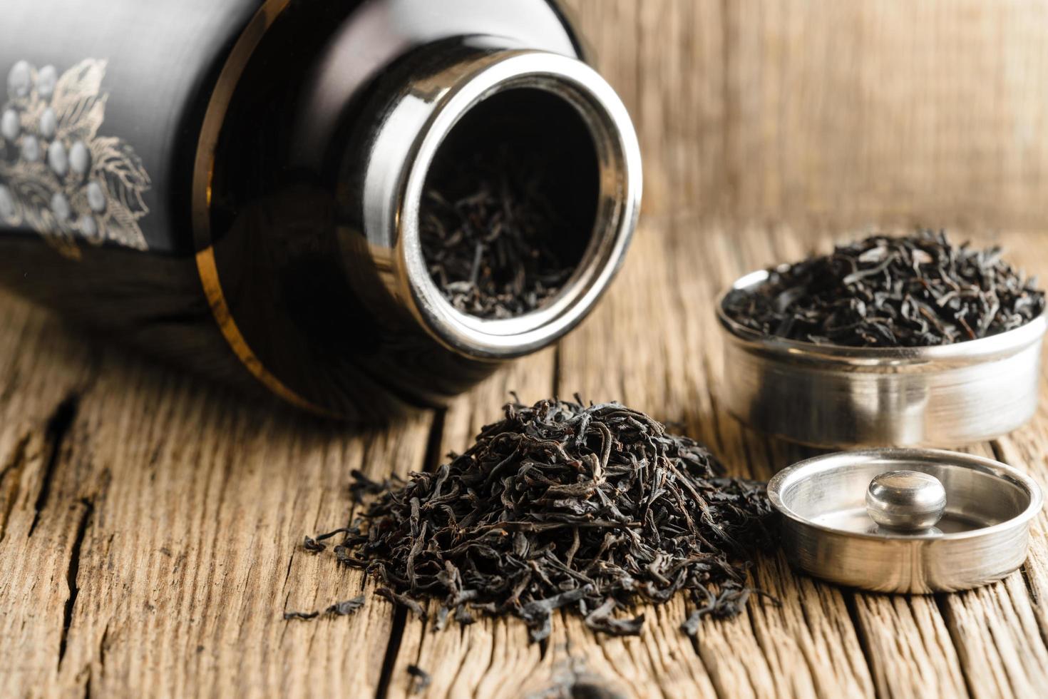 Hoja grande de té negro sobre la vieja mesa rústica de madera foto