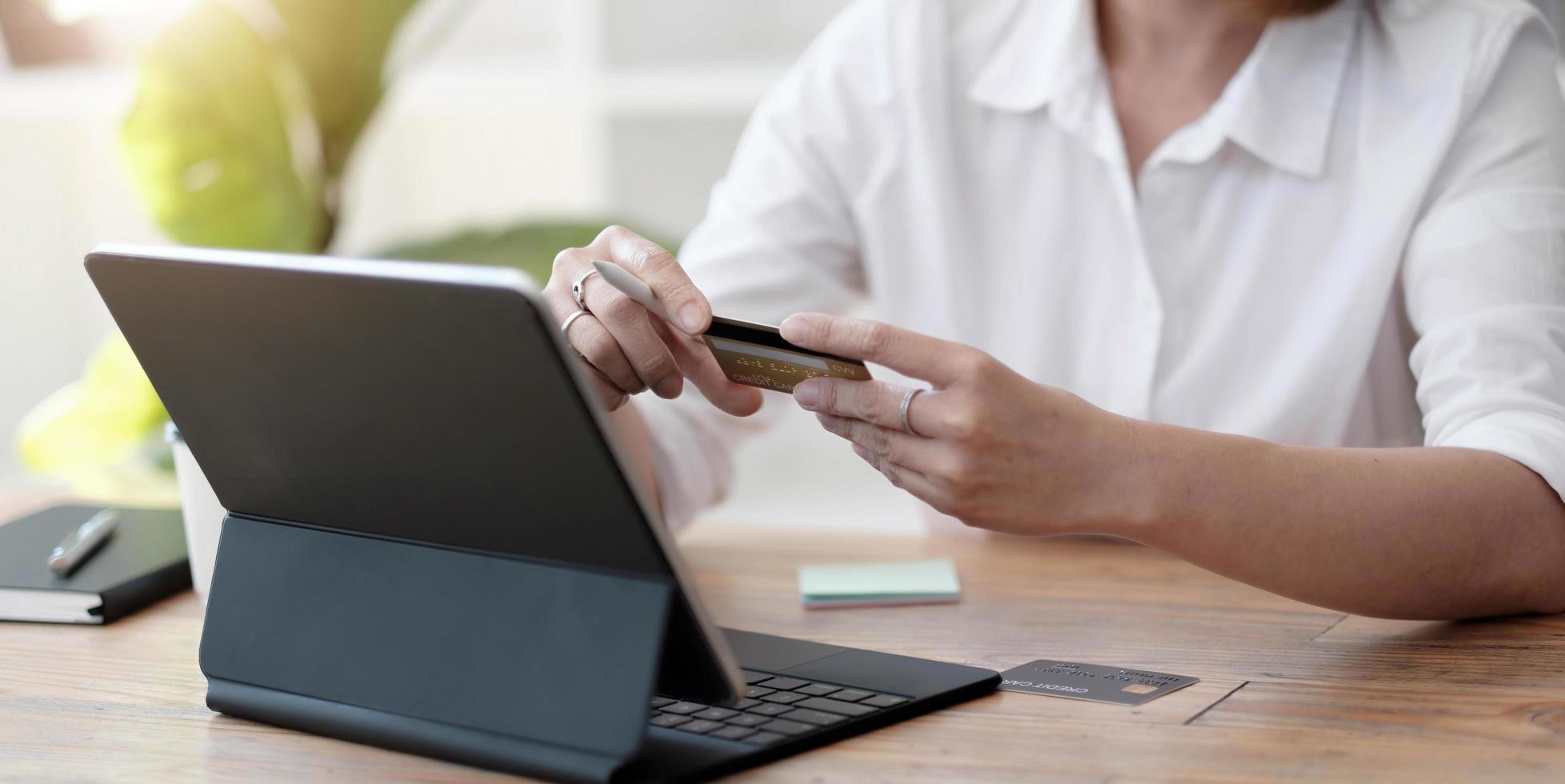 niña hace una compra en internet en la computadora con tarjeta de crédito foto