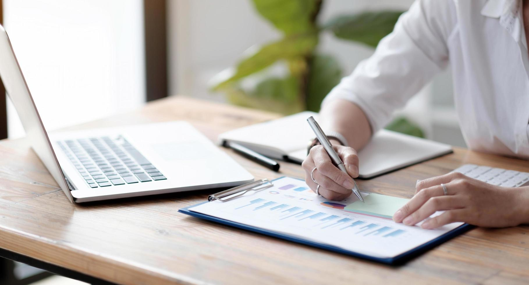 De cerca, un contador o propietario de un negocio escribe en notas adhesivas, toma notas en las notas de correos, trabaja en informes financieros y calcula los presupuestos comerciales. foto