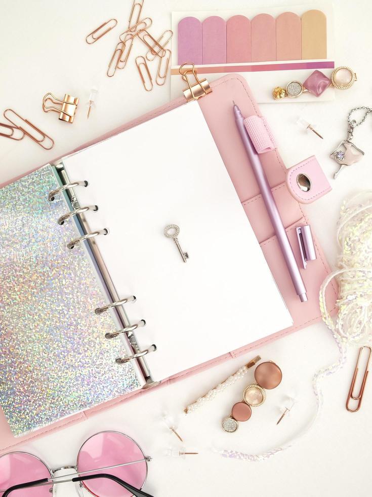 llave plateada en la página blanca del planificador. diario abierto con página blanca y holográfica. planificador rosa con lindos artículos de papelería. foto de decoración de planificador de glamour rosa