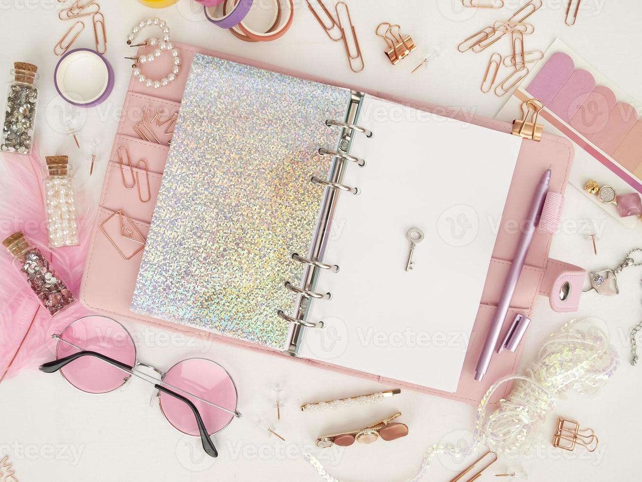 diario abierto con página blanca y holográfica. planificador rosa con lindos artículos de papelería. vista superior del planificador rosa con papelería. foto de decoración de planificador de glamour rosa