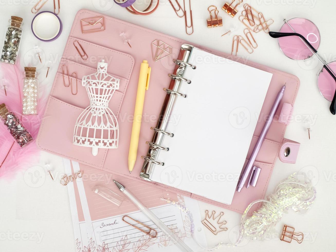 vista superior de un planificador rosa con lindos artículos de papelería. planificador de glamour rosa con una figura de maniquí blanco. planificador con páginas abiertas sobre un fondo blanco y con hermosos accesorios bolígrafos, botones, alfileres. foto