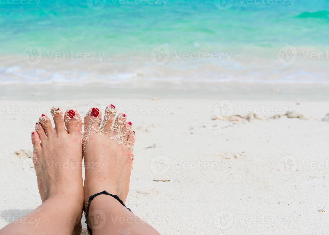 pies de mujer y uñas rojas en la playa foto