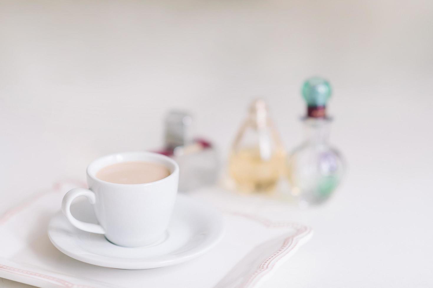 Taza blanca con café en un plato de porcelana en el fondo de los frascos de perfume. foto