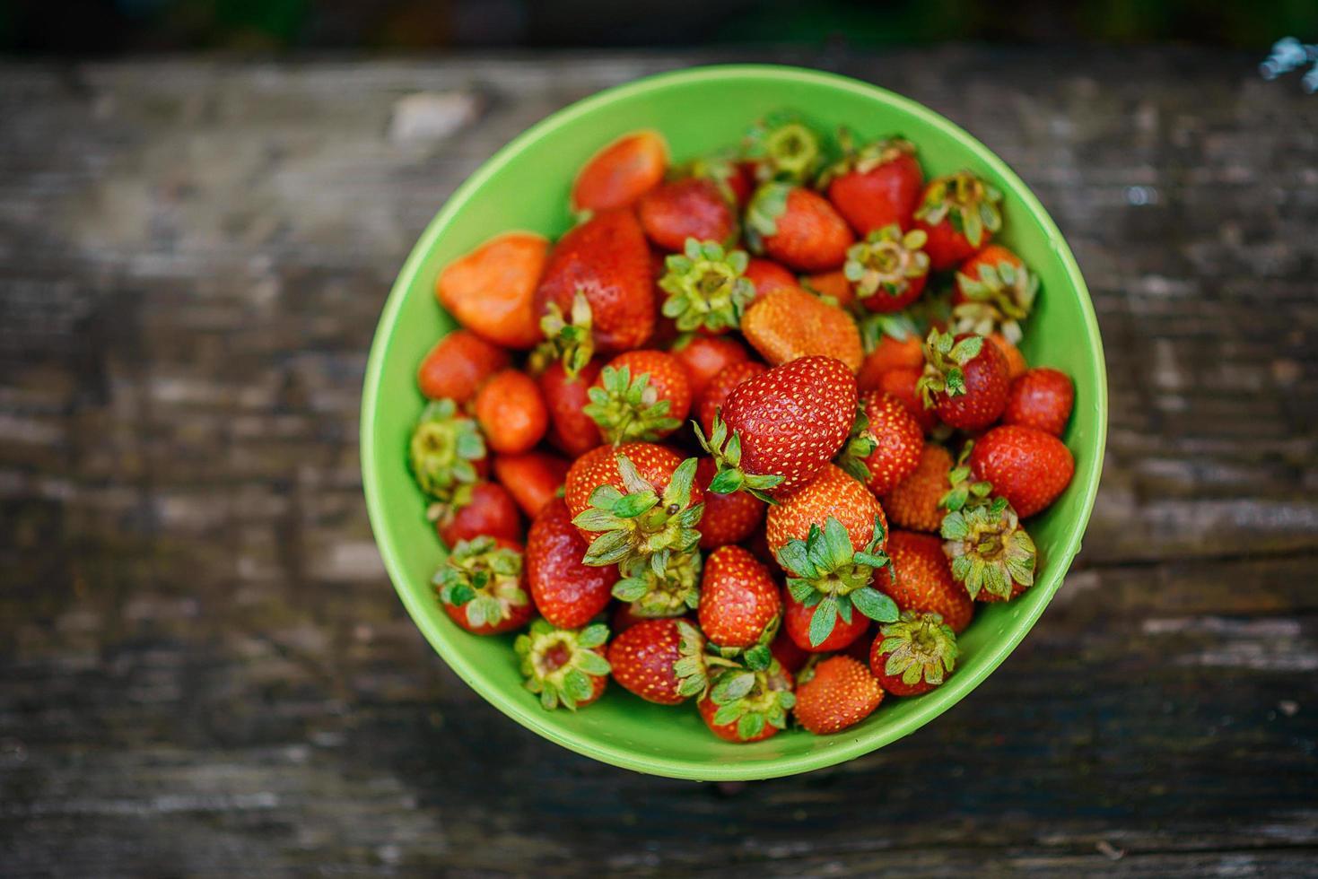 fresas maduras fragantes jugosas brillantes en una placa verde. foto