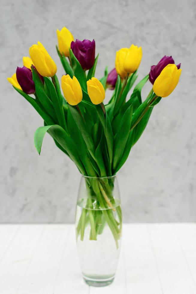 Ramo de flores de tulipán de primavera púrpura y amarillo en un jarrón de vidrio sobre un fondo claro. día de la Madre. día Internacional de la Mujer. foto