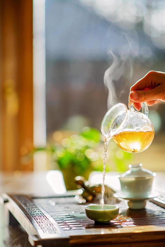 proceso de preparación del té, ceremonia del té, una taza de té verde oolong recién hecho, luz cálida y suave. enfoque suave. foto