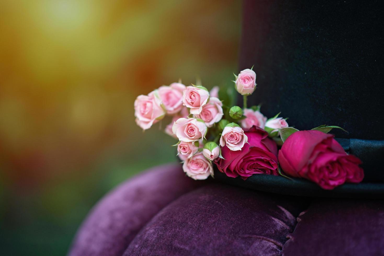 Alicia en el país de las Maravillas. sombrero cilíndrico decorado con flores rosas. de cerca. enfoque selectivo suave. foto