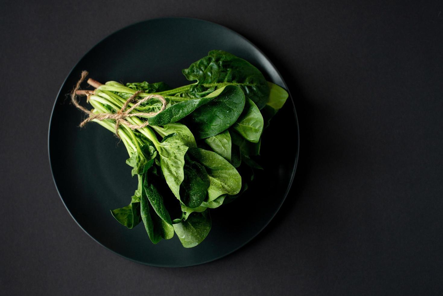 concepto de comida limpia. Manojo de hojas de espinacas orgánicas frescas en un plato sobre un fondo negro. Dieta saludable detox primavera-verano. comida cruda vegana. copie el espacio. foto