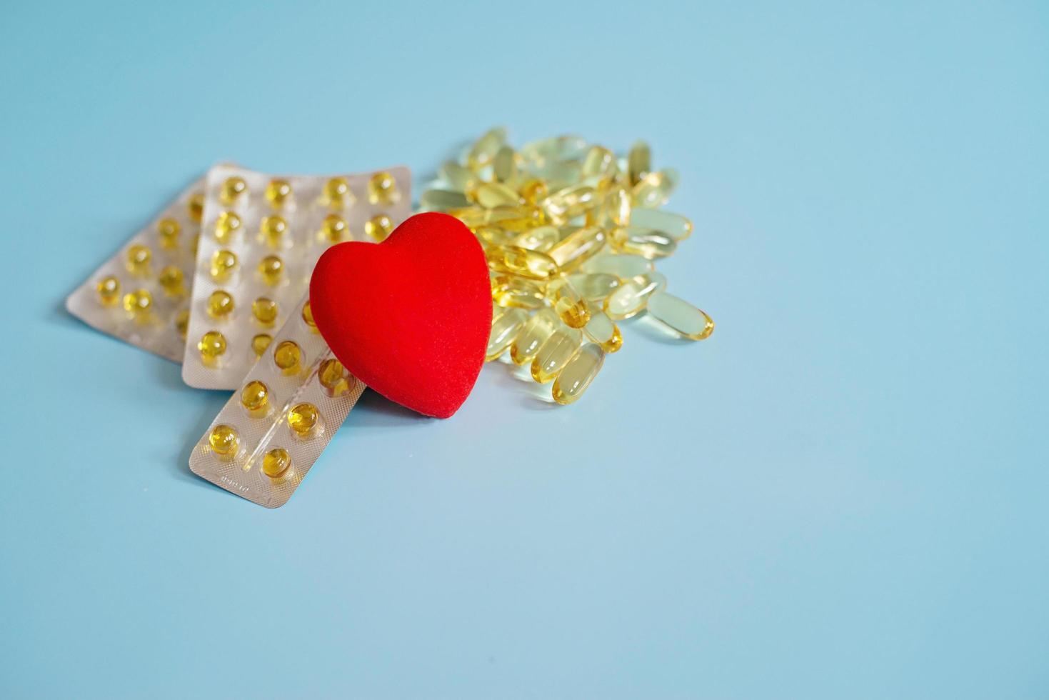 cápsulas de omega 3 con corazón rojo. aceite de pescado en tabletas. apoyo a la salud y tratamiento cardíaco. la medicina. foto