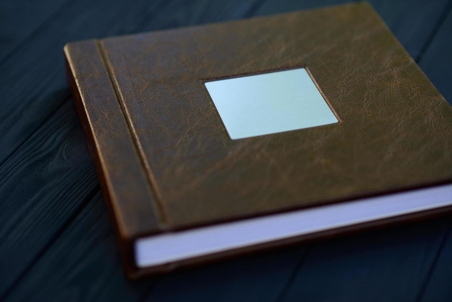 una placa de metal en la portada de un libro de fotos de cuero marrón sobre un fondo de madera negra.
