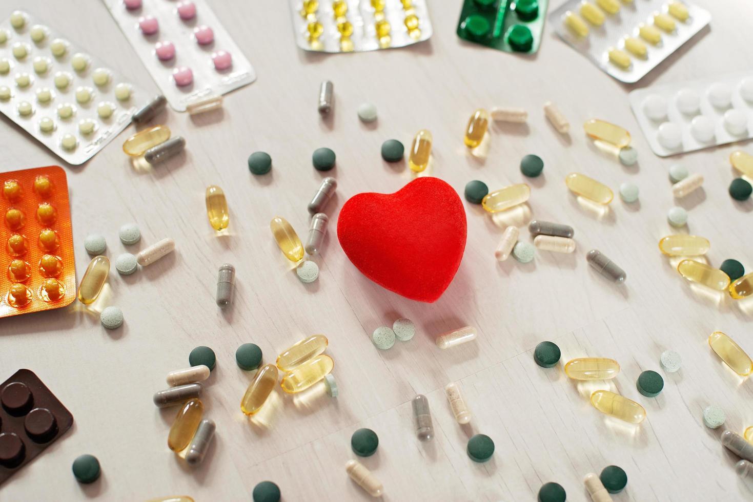 tema de farmacia, píldoras en cápsula con cápsulas de aceite de pescado omega 3 antibióticos medicinales y corazón rojo sobre un fondo claro. foto