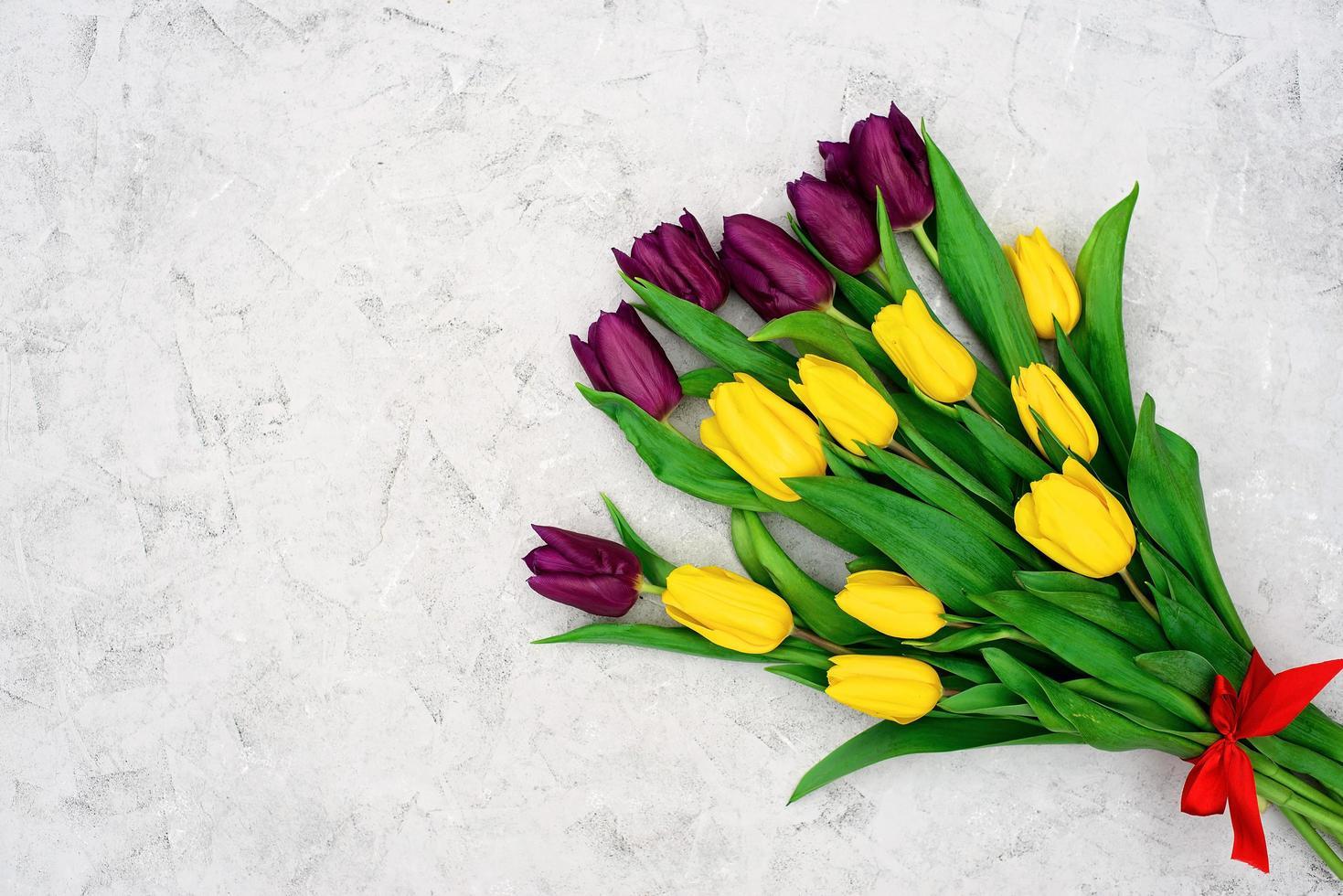 ramo de flores de tulipán de primavera amarillo y púrpura sobre un fondo de piedra clara. endecha plana. copie el espacio. día de la Madre. día Internacional de la Mujer. foto