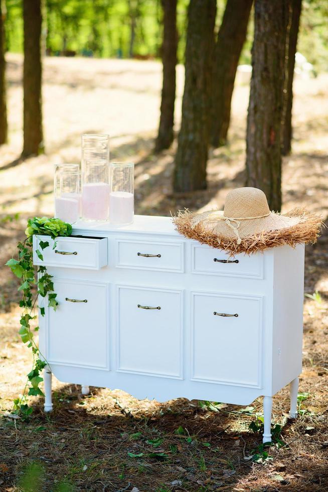 Hermosa cómoda blanca con sombrero de paja en el bosque. fiesta de chicas de estilo boho. foto