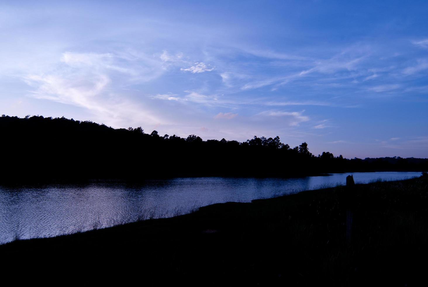 hermoso cielo paisaje con puesta de sol sobre la orilla del río foto
