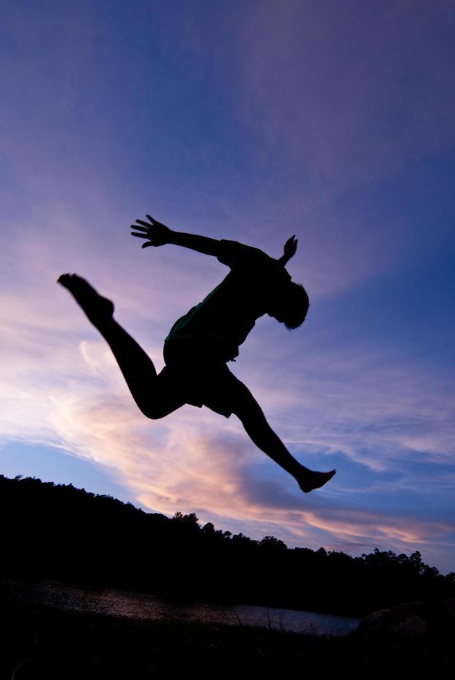 silueta feliz saltando contra hermosa en la puesta de sol. libertad, concepto de disfrute foto