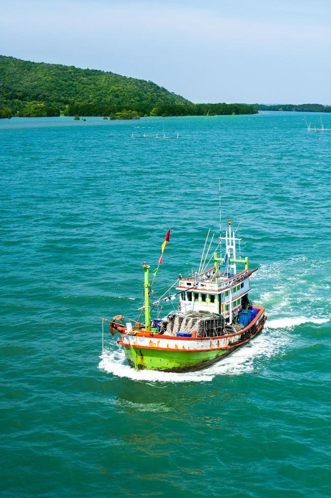 barco de pesca flotando en el mar azul del agua y el cielo foto