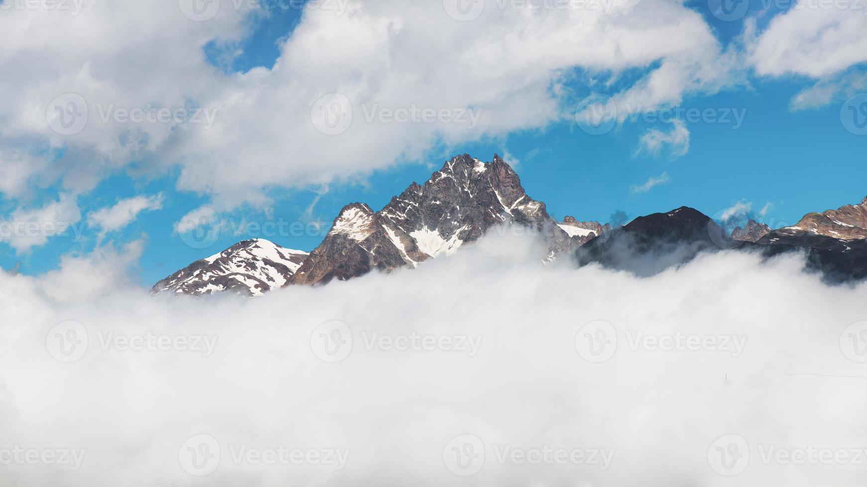 panorama de la cima de la montaña que sale de las nubes foto
